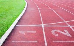 Αφετηρία αριθμών στην κόκκινη τρέχοντας διαδρομή, την τρέχοντας διαδρομή και την πράσινη χλόη Στοκ εικόνες με δικαίωμα ελεύθερης χρήσης