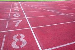 Αφετηρία αριθμών στην κόκκινη τρέχοντας διαδρομή, την τρέχοντας διαδρομή και την πράσινη χλόη Στοκ εικόνα με δικαίωμα ελεύθερης χρήσης