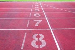 Αφετηρία αριθμών στην κόκκινη τρέχοντας διαδρομή, την τρέχοντας διαδρομή και την πράσινη χλόη Στοκ Εικόνες