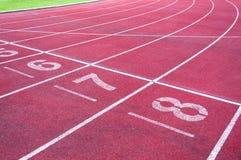 Αφετηρία αριθμών στην κόκκινη τρέχοντας διαδρομή, την τρέχοντας διαδρομή και την πράσινη χλόη Στοκ φωτογραφία με δικαίωμα ελεύθερης χρήσης