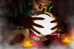 Αφηγητής τύχης γυναικών τσιγγάνων που εξετάζει τη σφαίρα κρυστάλλου Στοκ Εικόνα