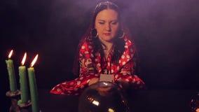 Αφηγητής τύχης τσιγγάνων στις κάρτες επιτραπέζιων δαπανών από το μαγικό κρύσταλλο απόθεμα βίντεο