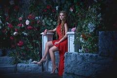 Αφηρημένες ανασκοπήσεις φαντασίας με το μαγικό βιβλίο Όμορφη πριγκήπισσα στην κόκκινη συνεδρίαση φορεμάτων σε έναν μυστικό κήπο Στοκ Φωτογραφίες