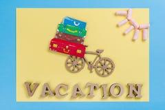 Αφηρημένες ξύλινες επιστολές διακοπών λέξης Μπλε κίτρινος υποβάθρου, εικόνα του σωρού των βαλιτσών στο ποδήλατο Στοκ Εικόνες