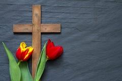 Αφηρημένες τουλίπες Πάσχας και ξύλινος σταυρός στο μαύρο μάρμαρο Στοκ Εικόνα