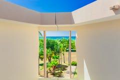 Αφηρημένη άποψη της αρχιτεκτονικής οικοδόμησης ξενοδοχείων μέσα στους τοίχους με το παράθυρο που οδηγεί στην τροπικούς παραλία κα Στοκ Φωτογραφία