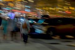 αφηρημένη ανασκόπηση Οδός, κορίτσι με ένα σακίδιο πλάτης πίσω σε μας και άλλους ανθρώπους κοντά στο χώρο στάθμευσης, θαμπάδα κινή Στοκ Φωτογραφίες