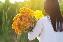 Αφηρημένη γυναίκα με τα λουλούδια ανθοδεσμών δονούμενα στα χέρια στο υπόβαθρο τομέων χλόης στοκ εικόνες