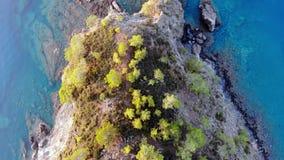 Αφηρημένη εναέρια άποψη των απότομων βράχων θάλασσας με τα μικρά δέντρα και τα κύματα απόθεμα βίντεο