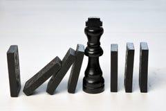 Αφηρημένη επιχειρησιακή έννοια με τα κομμάτια κομματιού σκακιού βασιλιάδων και ντόμινο πεσμένος Στοκ Εικόνες