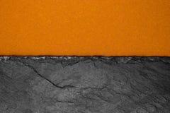Αφηρημένη σύνθεση υποβάθρου διαιρεσμένος στο μισό ματ σκούρο παρτοκαλί έγγραφο χρώματος και τη μαύρη πέτρα με το διάστημα αντιγρά στοκ εικόνες