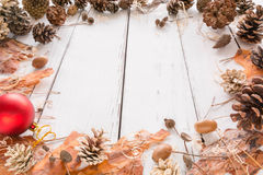 Αφηρημένο πλαίσιο Χριστουγέννων με τους κώνους, το φλοιό πεύκων, τα βελανίδια, και τα παιχνίδια άσπρος ξύλινος ανασκόπησης Στοκ Εικόνες