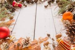 Αφηρημένο πλαίσιο Χριστουγέννων με τους κώνους, το φλοιό πεύκων, τα βελανίδια, και τα παιχνίδια άσπρος ξύλινος ανασκόπησης Στοκ φωτογραφία με δικαίωμα ελεύθερης χρήσης