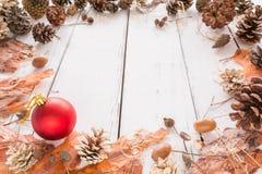 Αφηρημένο πλαίσιο Χριστουγέννων με τους κώνους, το φλοιό πεύκων, τα βελανίδια, και τα παιχνίδια άσπρος ξύλινος ανασκόπησης Στοκ Φωτογραφία