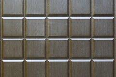 Αφηρημένο υπόβαθρο από τα τετράγωνα του καφετιού χρώματος Τεμάχιο ενός μετάλλου, μπροστινή πόρτα με τη μίμηση του ξύλου στοκ εικόνες