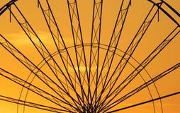 Αφηρημένο υπόβαθρο, μέταλλο-ρόδα ferris ενάντια στον ουρανό με το ηλιοβασίλεμα Στοκ Φωτογραφίες