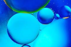 Αφηρημένο υπόβαθρο με τα ζωηρόχρωμα μπλε χρώματα κλίσης Πτώσεις πετρελαίου στην αφηρημένη psychedelic εικόνα σχεδίων νερού Στοκ Φωτογραφίες