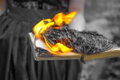 Αφηρημένο υπόβαθρο - το καίγοντας βιβλίο στα χέρια των γυναικών στοκ εικόνες