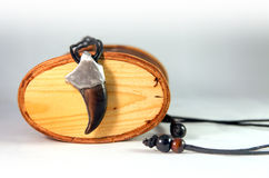 Αφορτε το κρεμαστό κόσμημα νυχιών με μια λαβή ξίφους μετάλλων ένα υπόβαθρο ενός woode Στοκ Φωτογραφία