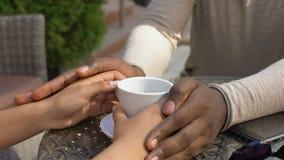 Αφρικανικά χέρια φίλων κτυπήματος ατόμων, ρομαντική ημερομηνία στον καφέ, έκφραση αγάπης απόθεμα βίντεο