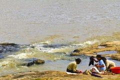Αφρικανικές γυναίκες που πλένουν τα ενδύματα σε έναν ποταμό Τα πλυμένα ενδύματα είναι ψέμα Στοκ φωτογραφία με δικαίωμα ελεύθερης χρήσης