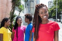 Αφρικανική γυναίκα με τα dreadlocks και φίλες στην πόλη στοκ εικόνα με δικαίωμα ελεύθερης χρήσης