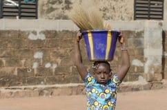 Αφρικανική γυναίκα που βοηθά την οικογένειά της ως έννοια παιδικής εργασίας Στοκ Φωτογραφίες