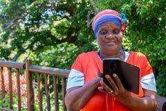 Αφρικανική γυναίκα που εξετάζει το κινητό τηλέφωνο της στοκ εικόνα