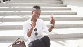 Αφρικανική γυναίκα που χρησιμοποιεί το έξυπνο τηλέφωνο καθμένος στα άσπρα σκαλοπάτια υπαίθρια απόθεμα βίντεο
