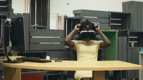 Αφρικανική γυναίκα στον εργασιακό χώρο που χρησιμοποιεί τα γυαλιά εικονικής πραγματικότητας απόθεμα βίντεο