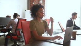 Αφρικανική επιχειρηματίας που απασχολείται στο σε απευθείας σύνδεση ηλεκτρονικό ταχυδρομείο δακτυλογράφησης που εξετάζει το lap-t απόθεμα βίντεο