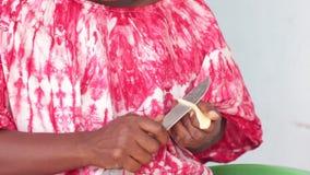 Αφρικανική συνεδρίαση γυναικών και τέμνουσα πατάτα στα μικρά κομμάτια απόθεμα βίντεο