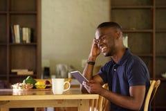 Αφρικανική συνεδρίαση ατόμων που χρησιμοποιεί στο σπίτι την ψηφιακή ταμπλέτα Στοκ φωτογραφία με δικαίωμα ελεύθερης χρήσης