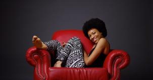 Αφρικανική συνεδρίαση γυναικών στην κόκκινη πολυθρόνα στοκ εικόνα