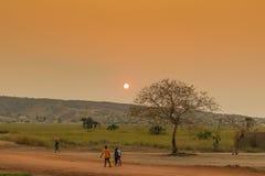 Αφρικανικοί αγροτικοί λαοί που επιστρέφουν από την εργασία, με το ηλιοβασίλεμα Sumbe  Στοκ φωτογραφία με δικαίωμα ελεύθερης χρήσης