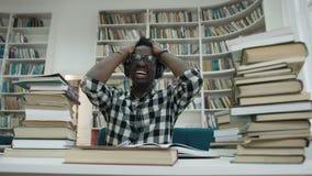 Αφρικανικός άνδρας σπουδαστής με τον πονοκέφαλο που ρίχνει τη μάνδρα αφότου τελειώνει τη διάλεξη στη βιβλιοθήκη φιλμ μικρού μήκους
