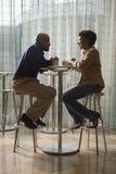 Αφρικανικός-αμερικανικό ζεύγος που έχει τον καφέ στον καφέ στοκ φωτογραφία