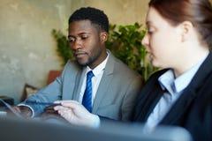 Αφρικανικός επιχειρηματίας που ακούει το συνάδελφο στη συνεδρίαση Στοκ φωτογραφία με δικαίωμα ελεύθερης χρήσης