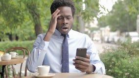 Αφρικανικός επιχειρηματίας που ανατρέπεται από την απώλεια σε Smartphone, που κάθεται στον υπαίθριο καφέ απόθεμα βίντεο