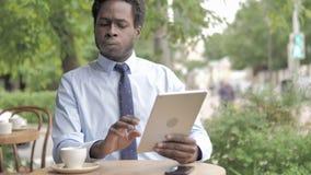 Αφρικανικός επιχειρηματίας που ανατρέπεται από την απώλεια στην ταμπλέτα, που κάθεται στον υπαίθριο καφέ φιλμ μικρού μήκους