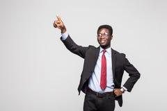 Αφρικανικός επιχειρηματίας που δείχνει σε κάτι στο άσπρο υπόβαθρο Στοκ Εικόνα