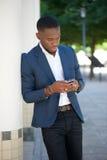 Αφρικανικός επιχειρηματίας που στέλνει το μήνυμα κειμένου στο κινητό τηλέφωνο Στοκ εικόνες με δικαίωμα ελεύθερης χρήσης