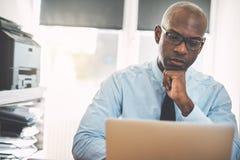 Αφρικανικός επιχειρηματίας σκληρός στην εργασία on-line σε ένα γραφείο Στοκ φωτογραφία με δικαίωμα ελεύθερης χρήσης