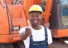 Αφρικανικός εργάτης οικοδομών με τον κόκκινο εκσκαφέα που παρουσιάζει αντίχειρα Στοκ Εικόνες