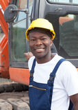 Αφρικανικός εργάτης οικοδομών με τον κόκκινο εκσκαφέα στο εργοτάξιο οικοδομής Στοκ Εικόνες