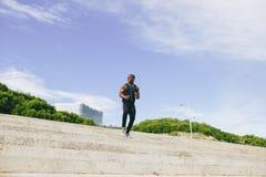 Αφρικανικός μαύρος αθλητικός τύπος που τρέχει προς τα πάνω με την ενέργεια στους λευκαντές σταδίων Στοκ Φωτογραφίες