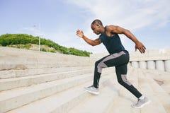 Αφρικανικός μαύρος αθλητικός τύπος που τρέχει προς τα πάνω με την ενέργεια στους λευκαντές σταδίων Στοκ φωτογραφία με δικαίωμα ελεύθερης χρήσης