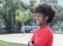 Αφρικανικός νέος ενήλικος με το χαρακτηριστικό afro hairstyle που κοιτάζει λοξά Στοκ Εικόνες