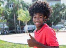 Αφρικανικός νέος ενήλικος με το χαρακτηριστικό afro hairstyle που παρουσιάζει αντίχειρα Στοκ Φωτογραφίες