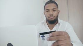 Αφρικανικός νεαρός άνδρας που ψωνίζει on-line με την πιστωτική κάρτα που χρησιμοποιεί το lap-top στο σπίτι φιλμ μικρού μήκους